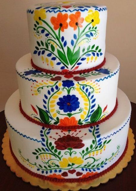 a bold Mexican-inspired hand painted wedding cake with red ribbons is amazing and chic