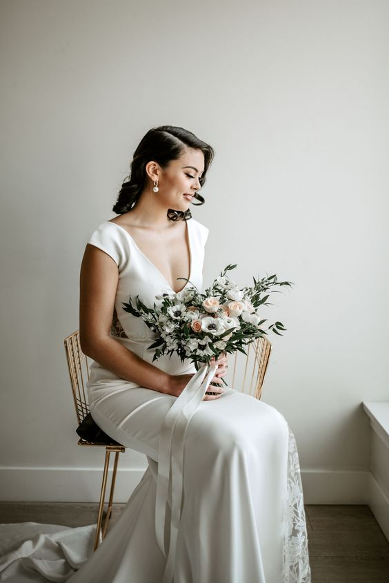 a modern glam bridal look with a plain fitting wedding dress with lace inserts, a deep neckline and cap sleeves plus statement pearl earrings