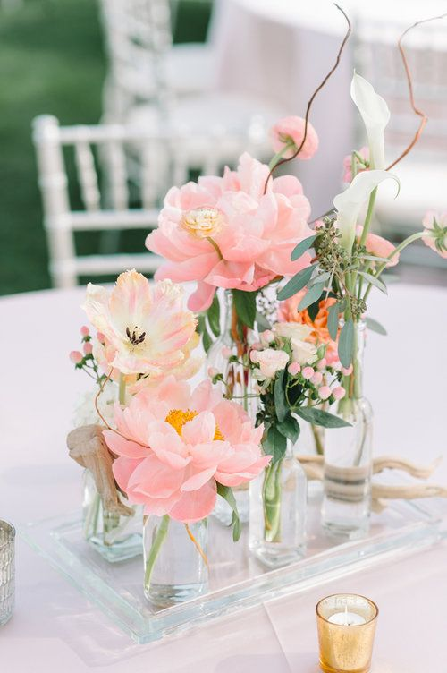 03 a beautiful cluster wedding centerpiece of clear bottles, blush peonies, white callas, greenery and twigs is a chic idea for spring or summer