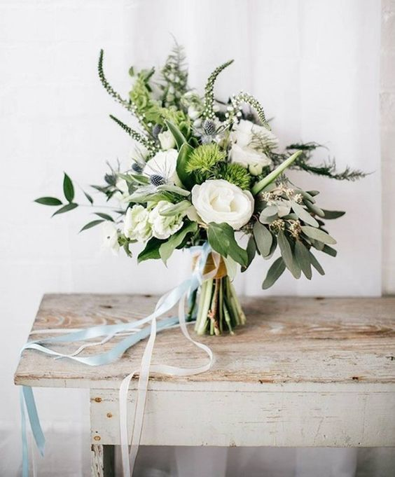 a beautiful modern wedding bouquet with white blooms, thistles, white astilbe and foliage is a beautiful and cool idea