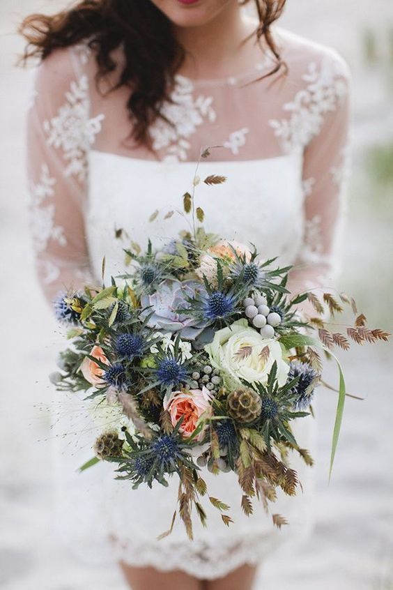 a bright and cheerful wedding bouquet with white and peachy blooms, thistles, berries and seed pods plus grasses