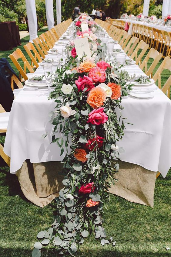 a beautiful wedding table runner with orange and pink peonies, white ones and lush greenery is bold