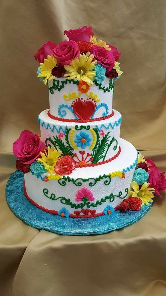 a bright Mexican wedding cake with bold floral patterns, bright fresh blooms is a traditional Mexican idea