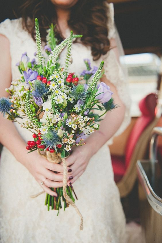 a bright and fun wedding bouquet with thistles, lilac and white blooms, berries and more details for an eye-catchy look