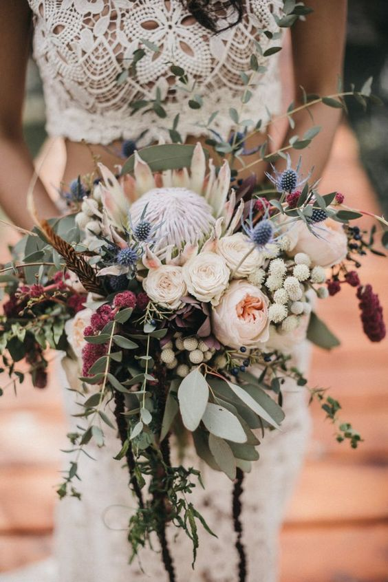 a cascading wedding bouquet with a king protea, blush roses, berries, amaranthus, eucalyptus for a fall wedding
