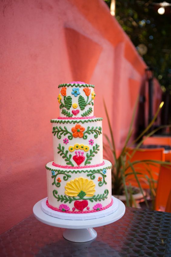 a chic and bold Mexican wedding cake with bold hand painting and pink ribbon detailing is a bright and fun idea