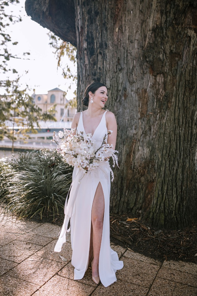 a modern glam bride wearing a plain A line wedding dress with no sleeves, a deep neckline and a front slit, nude shoes and statement earrings