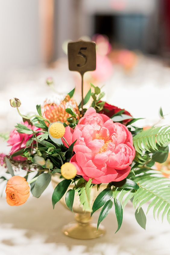 a bright wedding centerpiece with billy balls, coral peonies, orange blooms and foliage and fern leaves for a bold wedding