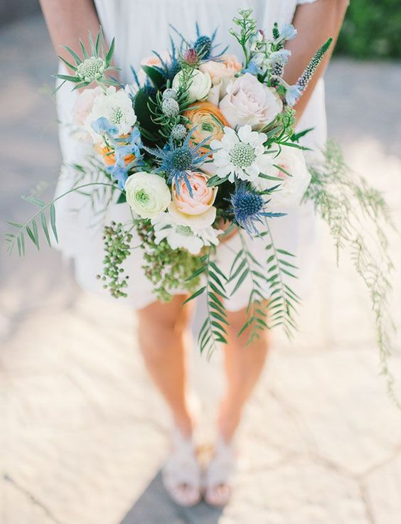 a cheerful wedding bouquet with white, blusha nd yellow blooms, thistles, cascading greenery and berries for a summer wedding
