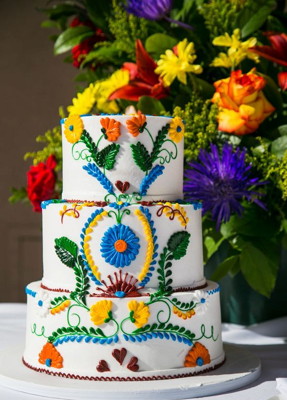 a chic and bright Mexican wedding cake with bold 3D botanical patterns and hearts is a fun idea