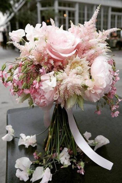 a delicate wedding bouquet with blush peonies and some other blooms plus blush astilbe and white ribbons is very chic