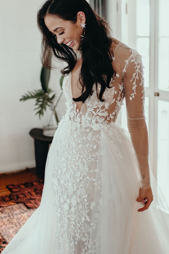 07 a modern luxurious bride wearing a sheath floral lace wedding dress with long sleeves and an overskirt plus statement earrings