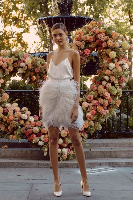 a chic reception look with a silk spaghetti strap top and a feather over the knee skirt plus statement earrings