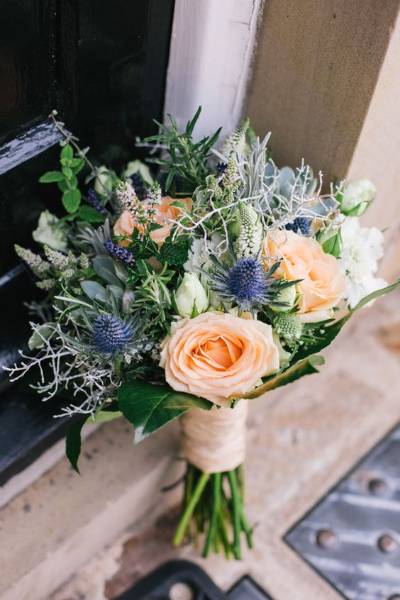 a chic wedding bouquet with peachy roses, white hydrangeas, greenery of various types and thistles is wow