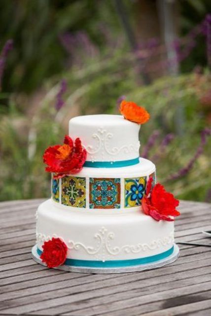 a colorful Mexican wedding cake in white, with turquoise ribbons, bold patterned edible tiles and bright sugar blooms