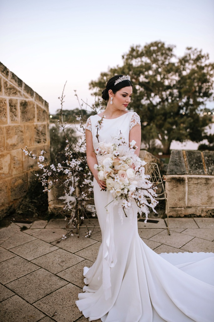 a modern luxurious bridal look with a plain mermaid wedding dress with lace applique sleeves and a train, a rhinestone tiara and statement earrings