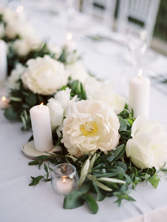 a classic and elegant wedding table runner with greeneyr, white peonies, tall and small candles in candleholders