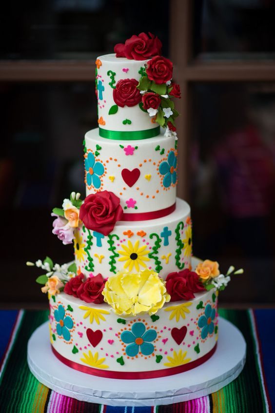 a colorful Mexican wedding cake with bold 3D floral and heart patterns, fresh blooms and leaves is a fun idea