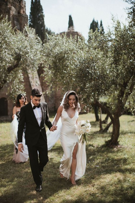 a modern refined wedding look with a silk slip wedidng dress with a depe neckline and a front slit plus a long veil is gorgeous