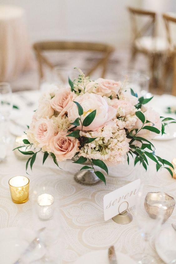 a classic wedding centerpiece of blush roses and a peony, greenery and blush hydrangeas in a silver bowl is amazing
