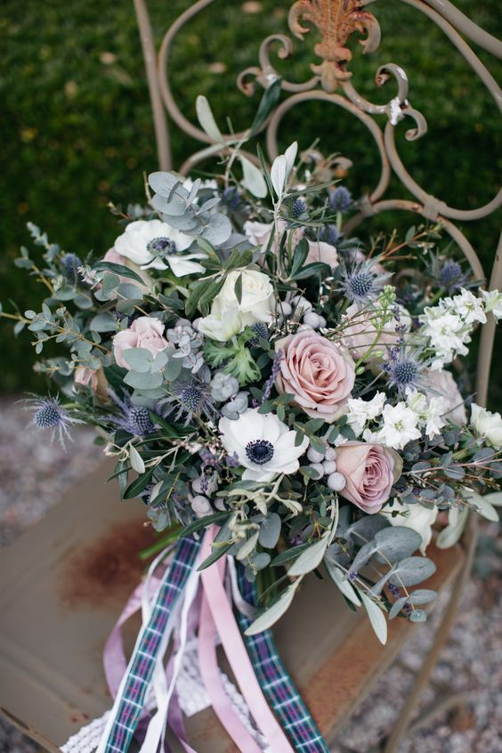 a delicate wedding bouquet with ligth pink roses, white anemones, thistles, berries and eucalyptus plus pink and plaid ribbons