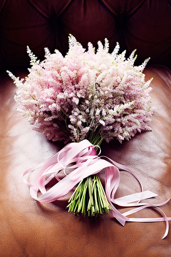 a refined blush astilbe wedding bouquet with pink ribbons is a stylish idea for a delicate bridal look
