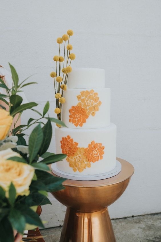 11 a bright and cool wedding cake in white, with orange and yellow brushstroke flowers and billy balls is a bold idea for a 70s wedding