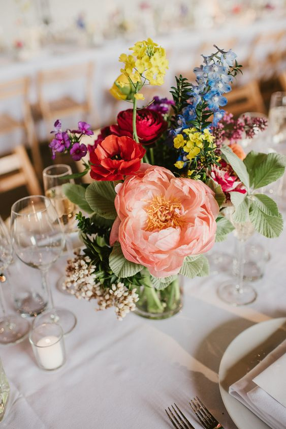 a colorful wedding centerpiece in red, purple, yellow, blue and pink with a lovely peony and greenery is gorgeous and fun