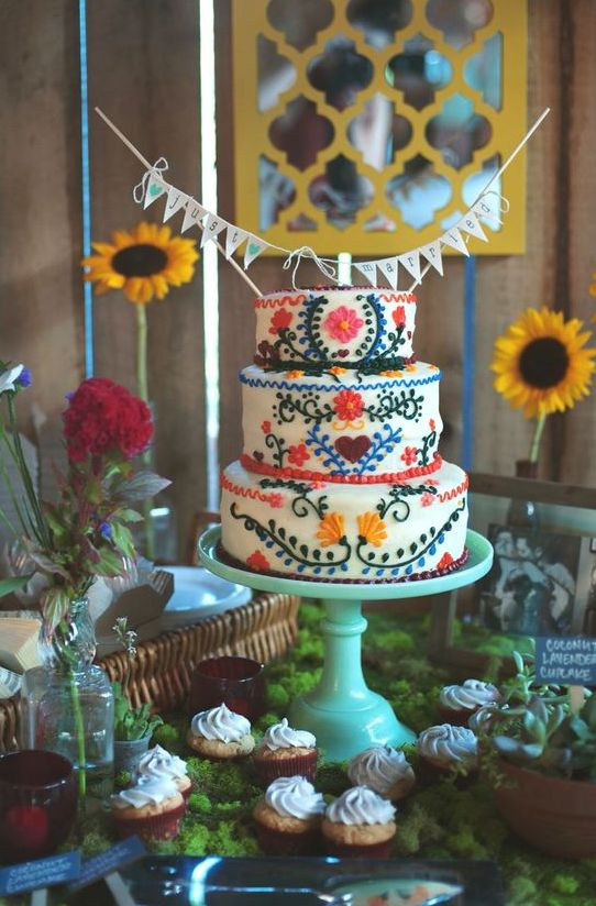 a colorful Mexican wedding cake with various bright floral patterns plus a banner topper is a fun idea to try