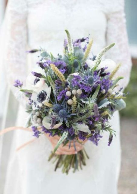 a gorgeous boho wedding bouquet with thistles, purple blooms, greenery and white anemones is amazing