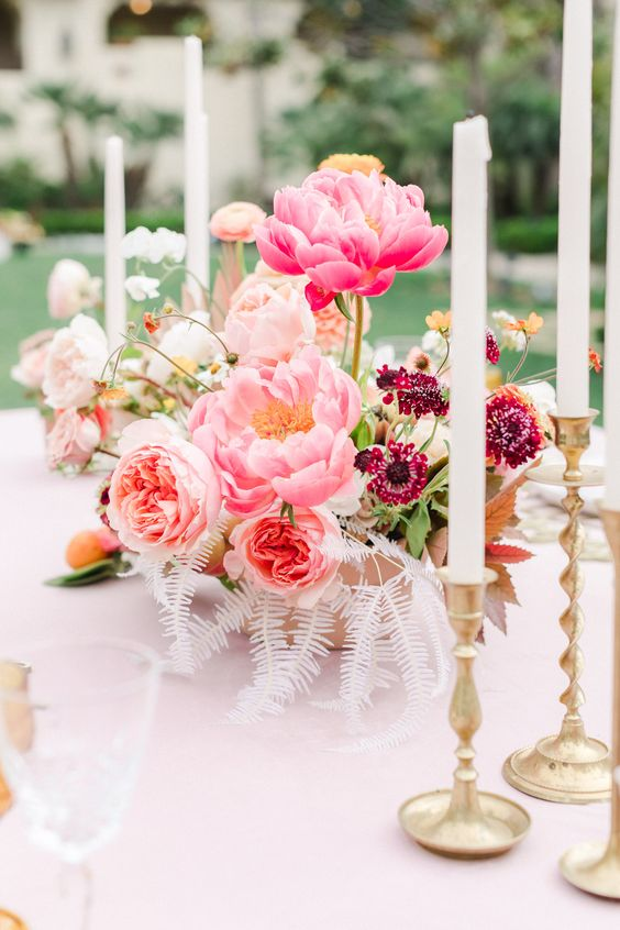 12 a whimsical wedding centerpiece with bold pink peonies, blush ones, burgundy and orange blooms and white leaves
