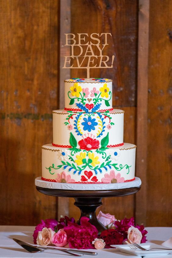 a fun and bold Mexican wedding cake with bright hand painted florals and botanicals plus a gold cake topper