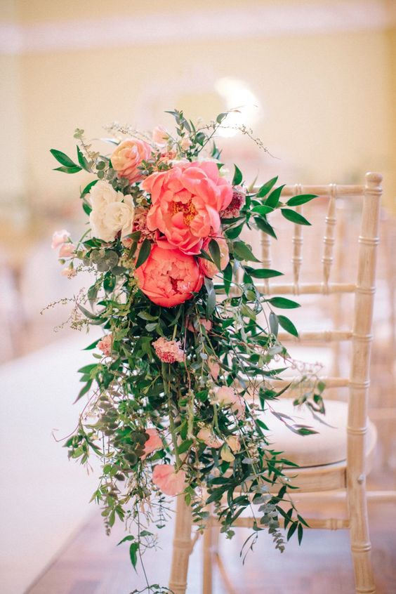 a wedding chair decorated with white blooms and coral peonies and with lush greenery is a pretty idea instead of a usual sign