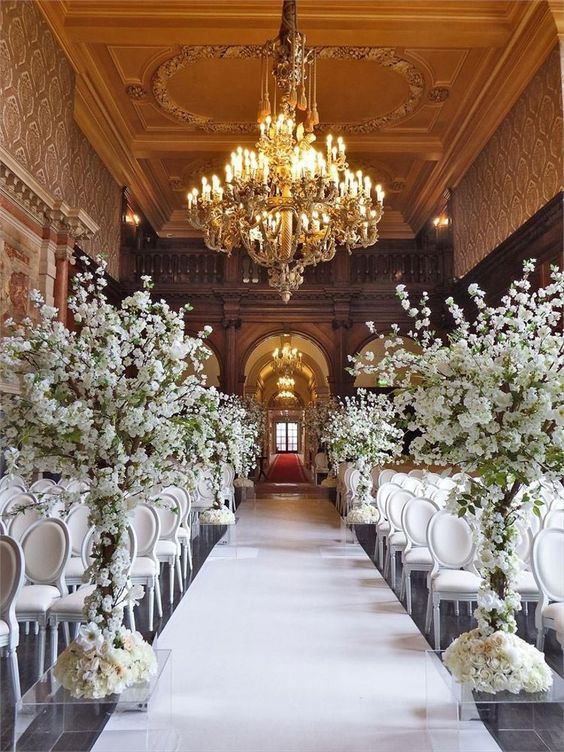 a jaw-dropping wedding ceremony space with refined white chairs, white blooming trees and a gorgeous gold chandelier