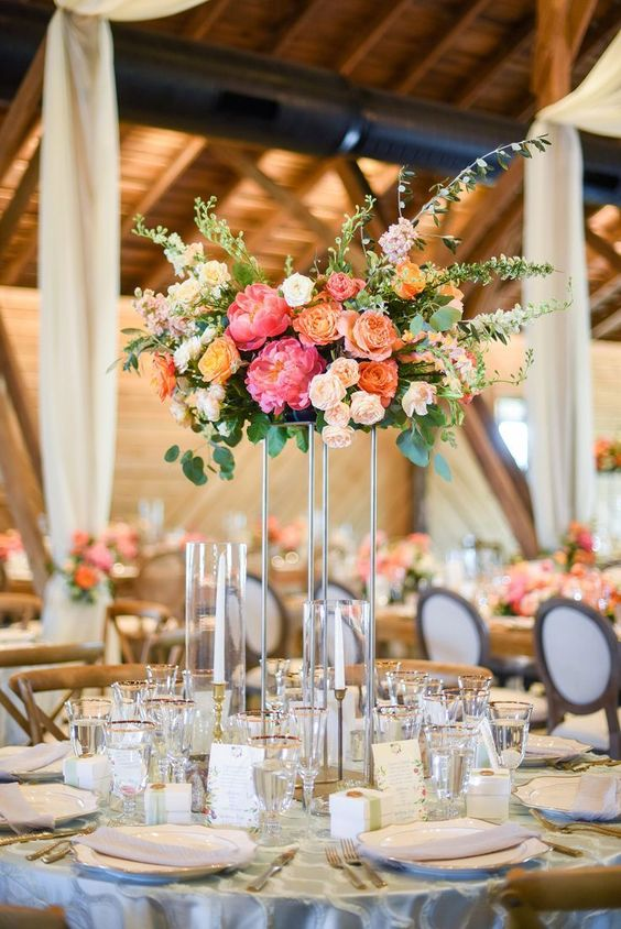 14 a vibrant tall wedding centerpiece with coral peonies, blush roses, orange and yellow blooms and greenery