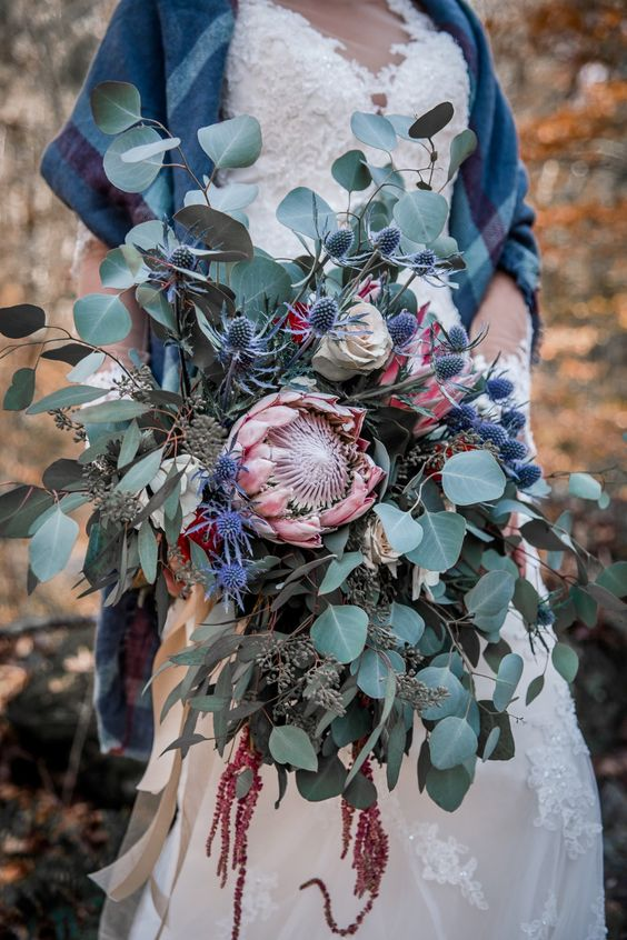 a jaw-dropping wedding bouquet with king proteas, thistles, amaranthus and lots of eucalyptus will make a statement