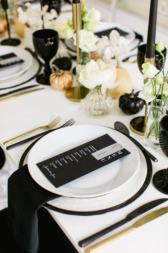 a modern glam Halloween wedding tablescape with a white table, black napkins, black candles, gold and black pumpkins and chic cutlery
