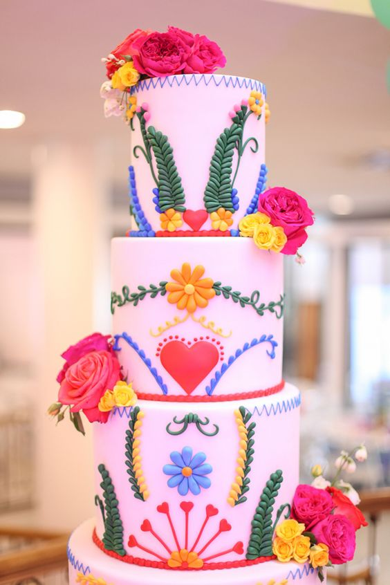 a pink wedding cake with bold floral and botanical patterns, bright blooms is a fun and cool idea for a Mexican wedding
