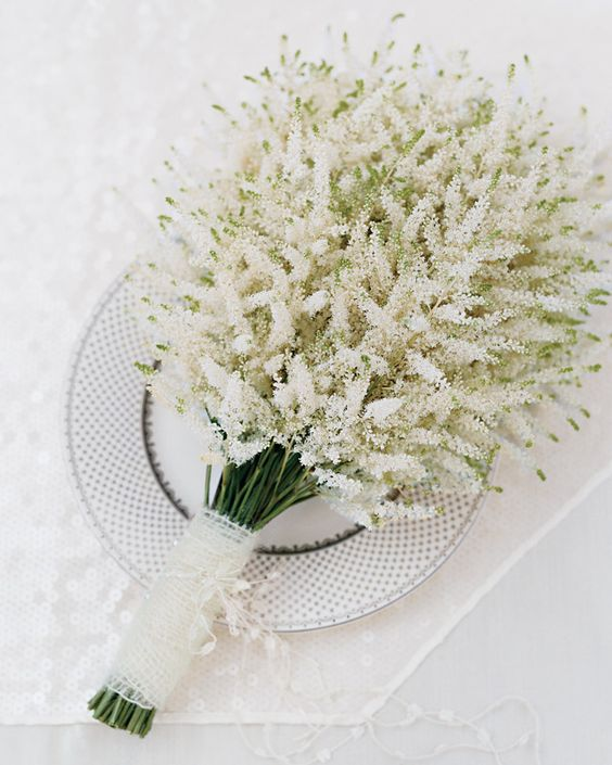 an airy and ethereal white astilbe wedding bouquet with a lace wrap is a stylish idea for a bride who wants something non-typical