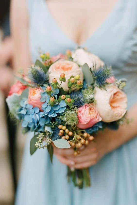 a lovely pastel wedding bouquet with blue hydrangeas, blush and coral roses, thistles and eucalyptus is amazing for spring or summer