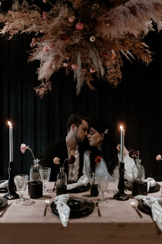 16 a modern glam rock wedding tablescape in dusty pink and blackm with a cluster wedding centerpiece, candles and black plates