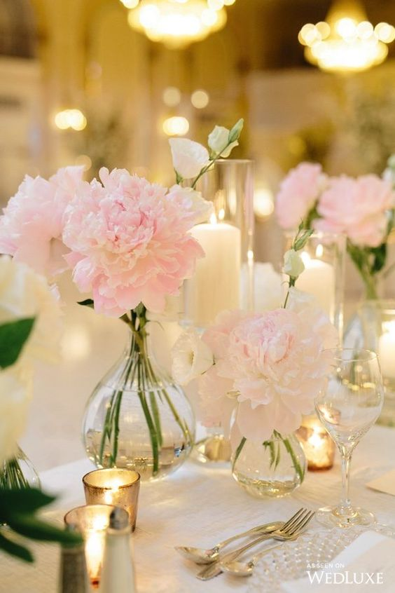 a tender wedding centerpiece with blush peonies, candles in small candleholders and in tall glass ones is very chic