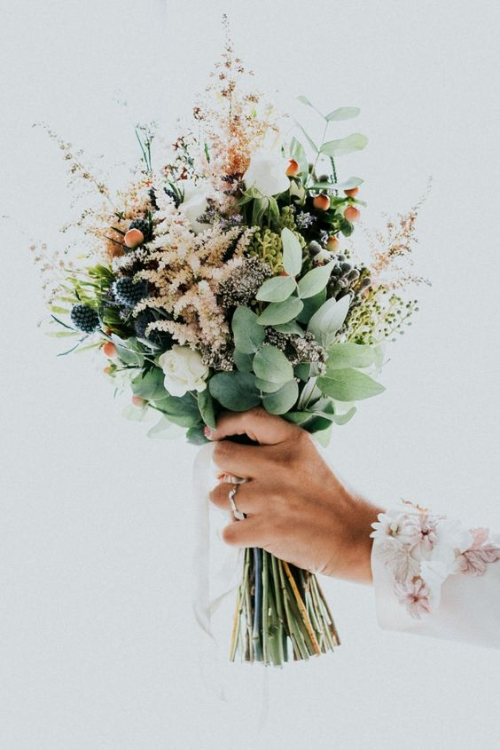 an adorable wedding bouquet with astilbe, thistles, greenery, white blooms, berries is fantastic and looks very textural and cool