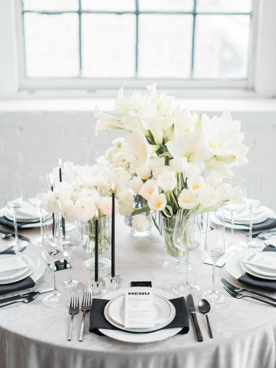 a modern glam wedding table in black and white, with matte cutlery, lush white blooms and thin black candles is super chic