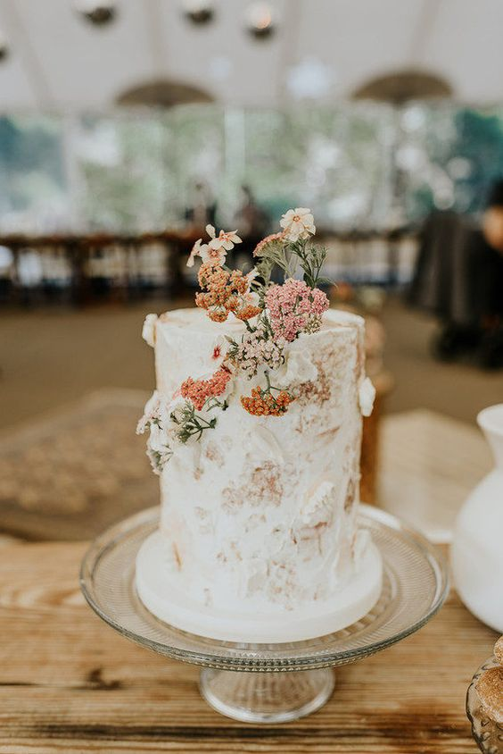 17 a neutral textural wedding cake with bold fresh wildflowers is a lovely idea for a 70s wedding with a strong boho feel
