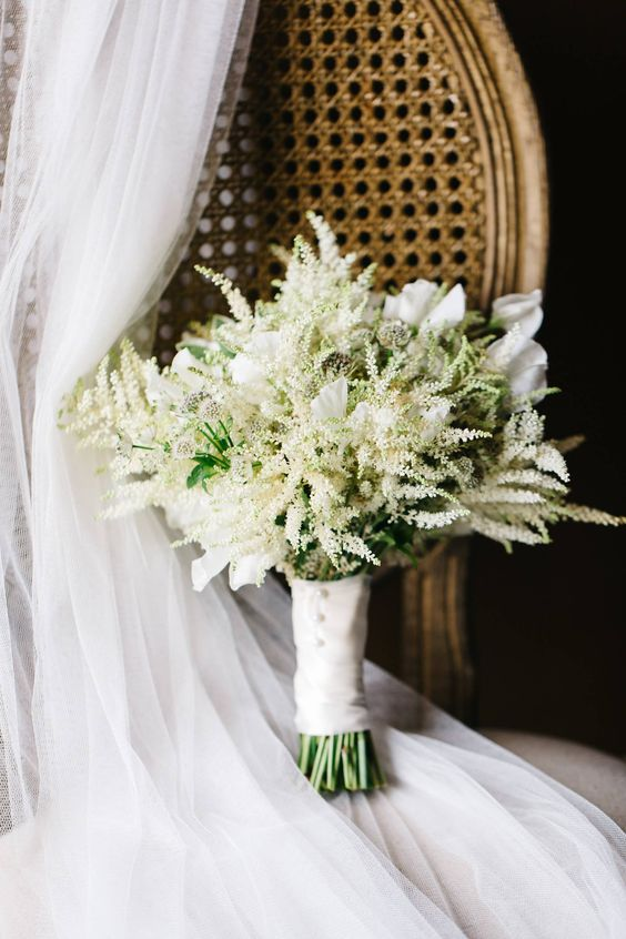 a white wedding bouquet with astilbe and lilies plus a white wrap on buttons for a fresh and beautiful spring or summer wedding bouquet