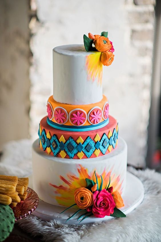 a bold Mexican wedding cake with colorful watercolors, a geometric 3D tier and a bold orange one plus fresh blooms
