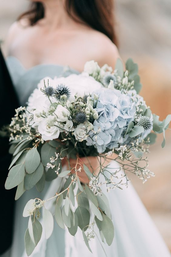 a lovely wedding bouquet with white roses, blue hydrangeas, lots of greenery and some mini blooms and thistles for a coastal bride