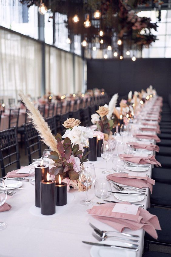 18 a modern glam wedding table with black candles, blush blooms with greenery and pampas grass, pink napkins and neutral cutlery