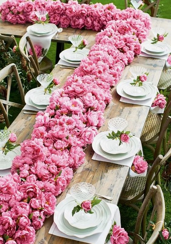 a simple spring wedding tablescape with a jaw-dropping pink peony runner and peonies marking each place setting is a gorgeous idea